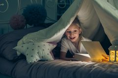 Girl opening a book. Lying in bed in the dark stock image