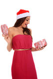 Girl opening a box. Girl with santa claus hat  surprises when opening a heart shape box Stock Images