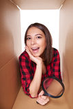 Girl opening a carton box and looking inside Royalty Free Stock Photos