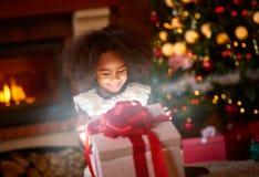 Girl opening Christmas magic presents. Surprise girl opening Christmas magic presents Royalty Free Stock Photo