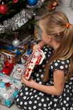 Girl opening Christmas present under Christmas tree Royalty Free Stock Image