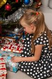 Girl opening Christmas present under Christmas tree Stock Photos