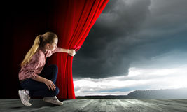 Girl opening curtain Royalty Free Stock Photography