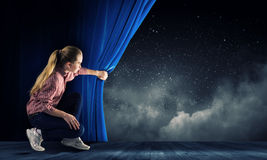 Girl opening curtain Stock Images
