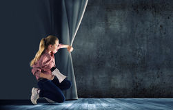 Girl opening curtain Royalty Free Stock Photo