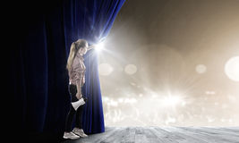 Girl opening curtain Stock Image