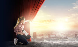 Girl opening curtain Stock Photos