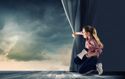 Girl opening curtain Royalty Free Stock Photos