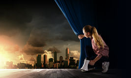 Girl opening curtain. Young woman in casual with megaphone opening curtain Stock Photo