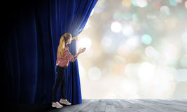 Girl opening curtain Stock Photography