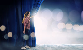 Girl opening curtain Royalty Free Stock Images
