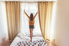 Weekend morning in hotel. Girl opening curtains in hotel room in the morning. Lazy weekend morning concept royalty free stock photos
