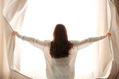 Girl opening curtains stock photos