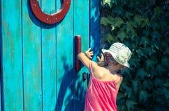 Girl opening door Stock Photography