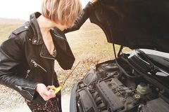 Girl opening the hood of her car checks the engine oil level. The blonde girl opens the hood of her car and checks the engine oil level. The concept of car Royalty Free Stock Photo
