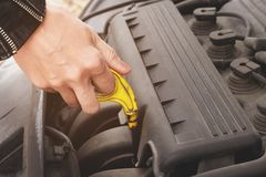Girl opening the hood of her car checks the engine oil level. Close-up of the hands The blond girl opens the hood of her car and checks the engine oil level. The Royalty Free Stock Image