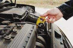 Girl opening the hood of her car checks the engine oil level. Close-up of the hands The blond girl opens the hood of her car and checks the engine oil level. The Stock Images