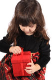 Girl opening present. Cute three year old little girl dressed up in a fancy dress  opening a red giftbox on a white background Stock Images