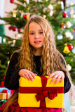 Girl opening present on Christmas day Stock Image