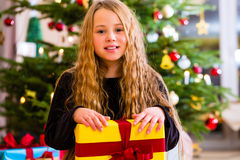 Girl opening present on Christmas day Stock Photography