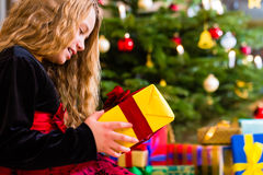Girl opening present on Christmas day Royalty Free Stock Images