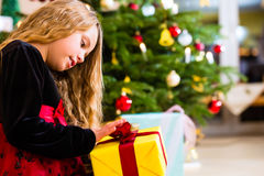 Girl opening present on Christmas day Stock Photos