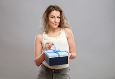 Girl opening a present isolated. Girl opening present isolated on grey background Royalty Free Stock Photography