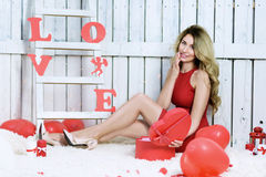 Girl opening a red gift box in shape of a heart Stock Photo