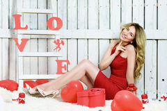 Girl opening a red gift box in shape of a heart Royalty Free Stock Image