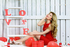Girl opening a red gift box in shape of a heart Royalty Free Stock Images
