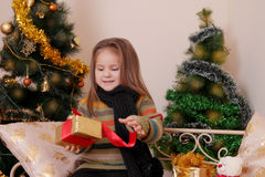 Girl opening red giftbox over golden Christmas tree Royalty Free Stock Photography