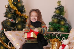 Girl opening red giftbox over golden Christmas tree Stock Images
