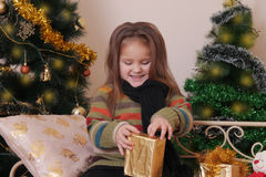 Girl opening red giftbox over golden Christmas tree Stock Photos