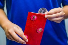 Girl opening Red Packet. A close up of a girl removing a Litecoin coin from a traditional red packet Royalty Free Stock Photo