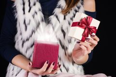 Girl opening red present box and light with ray out of boxes royalty free stock image