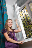 Girl opening window. At home Royalty Free Stock Image