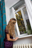 Girl opening window Stock Photography