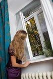 Girl opening window Stock Photography