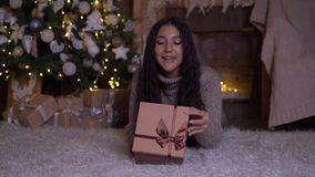 The girl opens the box with a gift and rejoices lying on the floor near the Christmas tree. 4K. The girl opens the box with a gift and rejoices lying on the stock video