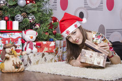 Girl opens the box with a new year gift and lies near the Christmas tree Stock Images