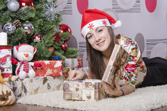 Girl opens the box with a new year gift and lies near the Christmas tree Royalty Free Stock Photos