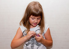Girl opens candy. Teen girl hardly opens candy Royalty Free Stock Image