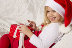 Girl opens a Christmas gift Royalty Free Stock Photography