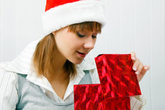 Girl opens a Christmas present Stock Photos