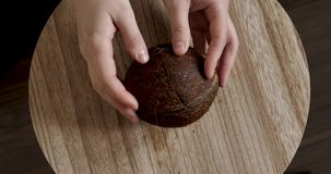 Girl opens coconut on the table