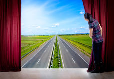 Girl opens the curtain and looking at the highway Stock Images