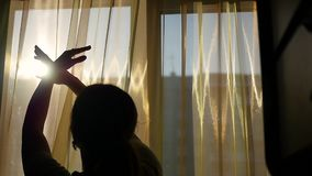 The girl opens the curtains and played with his hands through the sun`s rays. silhouette of a girl stock video