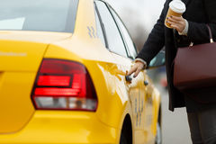 Girl opens door of taxi. Girl with coffee in hand opens door of yellow taxi Royalty Free Stock Image