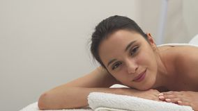 Girl opens eyes on the massage table royalty free stock image