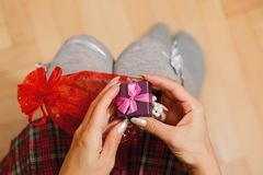 Girl opens gift box on her knees. Teenage female person in schoolgirl skirt unpacking gift - pearl bracelet in tiny box with bow holding it on her knees. Saint Royalty Free Stock Photography